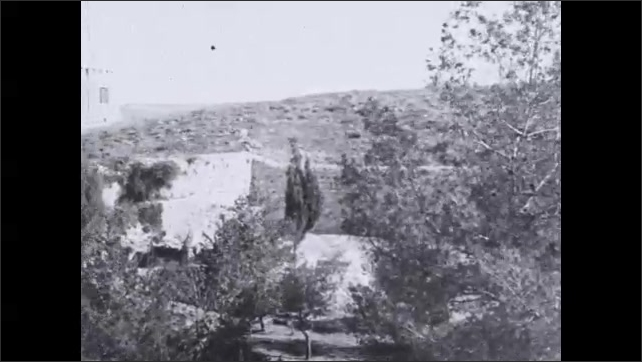 1930s: Stone wall lining hill and around buildings in Jerusalem.