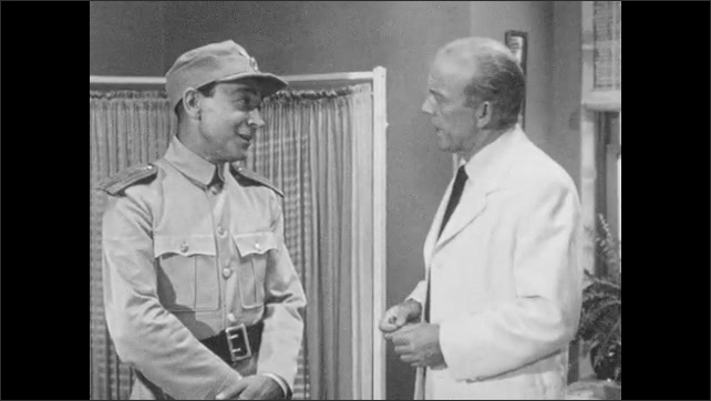 1950s: Men in military uniforms take medical supplies from cabinet. Man in military uniform and doctor talk to each other.