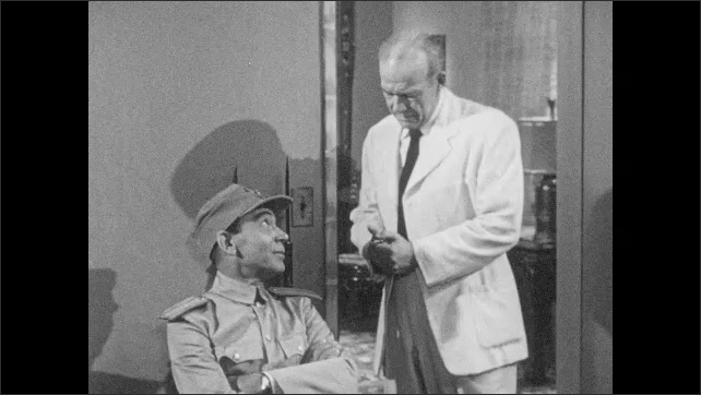 1950s: Man in military uniform walks to chair, sits down, talks. Man in white coat talks to military man.