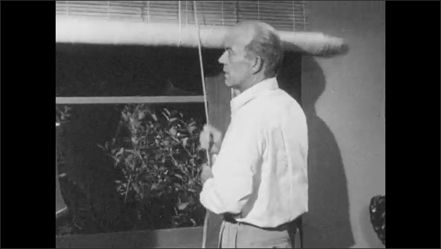 1950s: Man opens blinds. Man outside window points. Man closes blinds, peeks through curtain, talks.