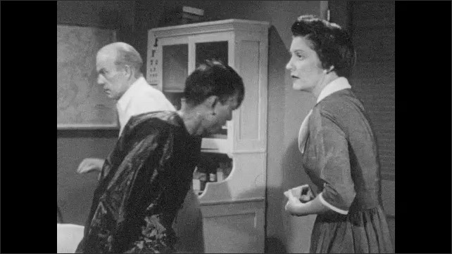 1950s: Chinese man sits on exam table, talks to white man and woman. Man and woman exit room, look at each other nervously.