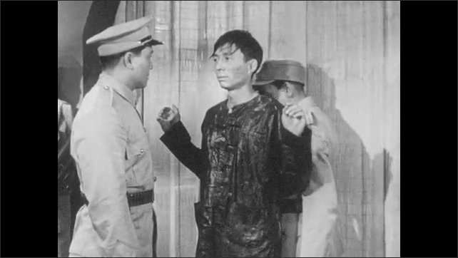 1950s: Man stands behind man in military uniform, talks. Man in uniform walks around Chinese man, gestures soldiers to stand down, talk to Chinese man.