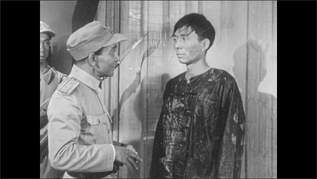 1950s: Man holds hand, looks down. Chinese military man questions Chinese man. Men talk.