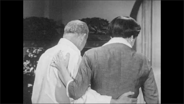 1950s: Woman runs through curtain, hugs man, cries. Man and woman walk slowly into next room, look at cross on desk.
