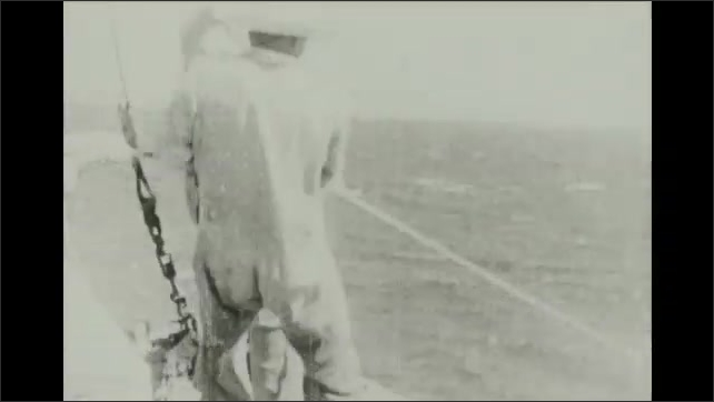 1930s: Man on boat holds up chunk of shark on hook. Men on bow of boat pull on rope in sea.