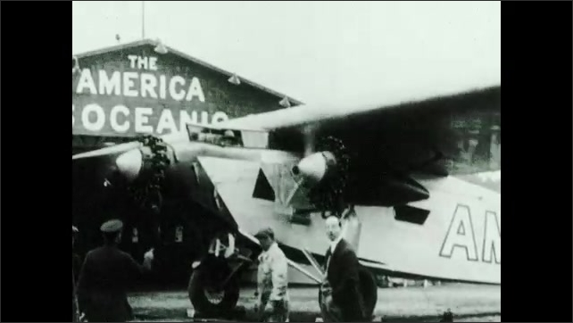1930s: Plane takes off.  Men stand in front of plane.  Man puts on hat.