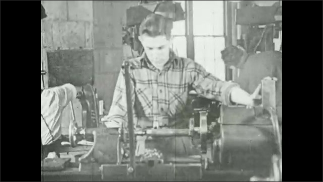 1940s: Man working at machine. Metal turning in machine. Man at machine. Metal turning in machine. Man puts hand over his eye.