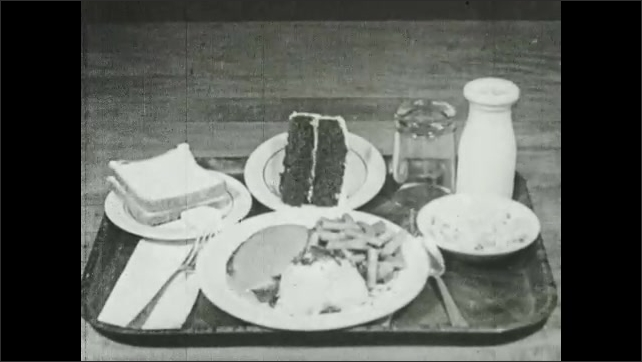 1940s: Close up of cooked chicken. Close up of orange pieces. Views of food on trays.