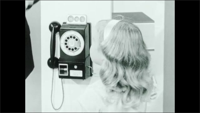 1960s: Man and ventriloquist dummy approach girl with toy pay phone. Man inserts dime into play phone and lifts handset. Man, puppet and girl talk near toy pay phone.