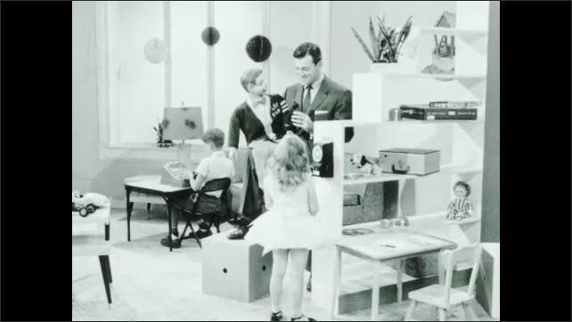 1960s: Girl turns crank on side of play phone. Man holds handset near puppet. Puppet speaks into phone.