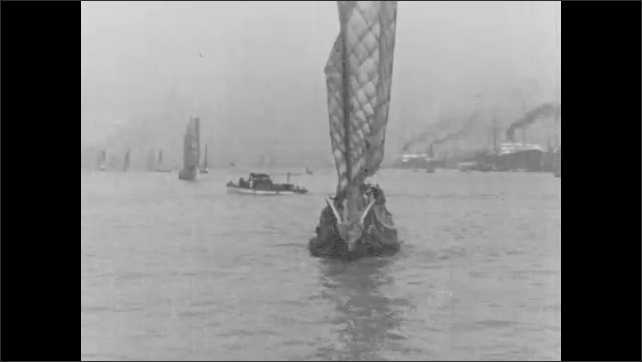 1920s: UNITED STATES: boats on moorings in bay. Sailing boat on water.