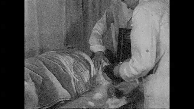 1930s: UNITED STATES: doctor takes patient's pulse. Doctor listens to pulse on patient