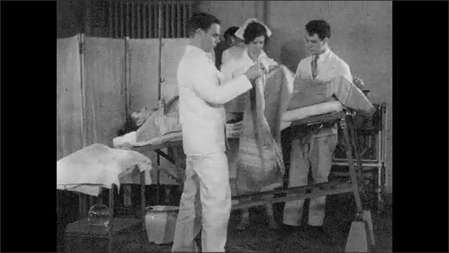 1930s: UNITED STATES: staff tip bed of patient. Nurse covers patient in blanket.