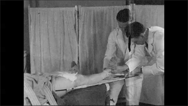 1930s: UNITED STATES: doctor attaches man's leg to splint.