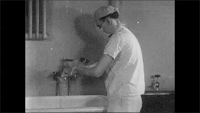 1930s: UNITED STATES: surgeon scrubs up before operation. Surgeon washes hands with soap.