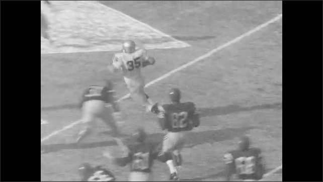 1960s: Football players play football, player scores a touchdown. Scoreboard. Player gets tackled.
