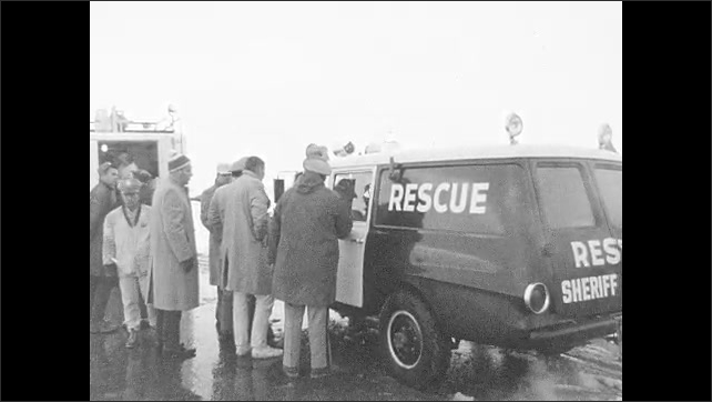 1960s: Cars parked on the side of the road. People lined up outside rescue vehicle. Officials talk to man. Mountains.