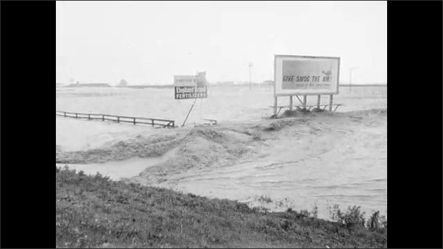 1960s: Man stands on road, shoots video. Car covered in flood waters. Washed out road. Flood waters.