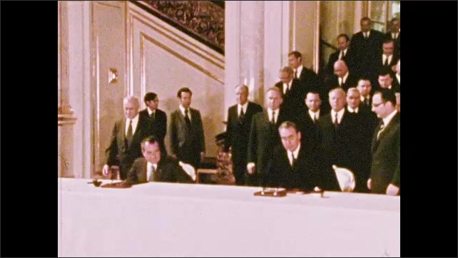 1970s: UNITED STATES: lady walks with peers. Men sit down to meeting. Chandelier in building. Men sign agreement