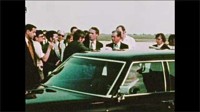 1970s: UNITED STATES: Man blows kiss to audience. Man on steps of private plane. Man wipes face with cloth. Men stand by car.