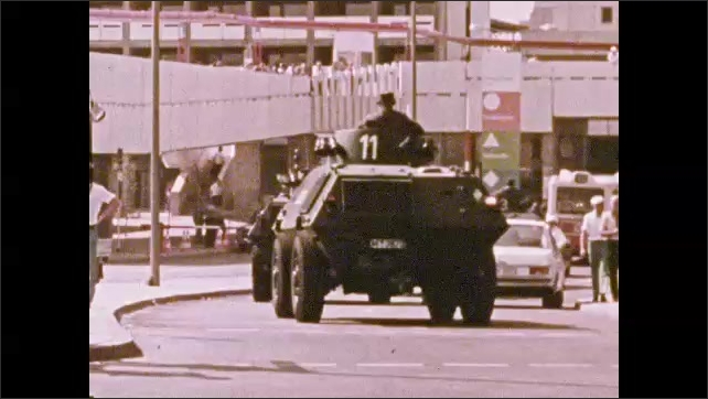 1970s: UNITED STATES: police guards crowd. Buildings in street. Tanks drive along street. Polizei helicopter.