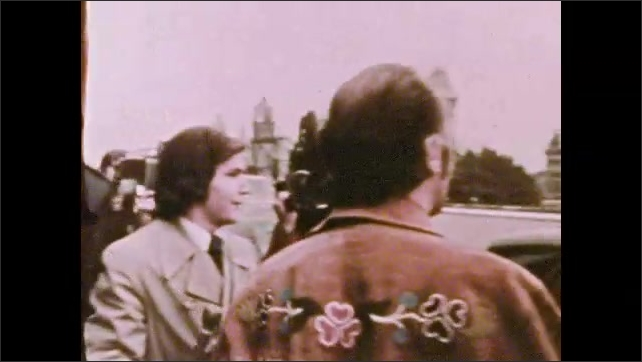 1970s: UNITED STATES: buildings in Germany. Man gets out of vehicle. Man speaks to press.