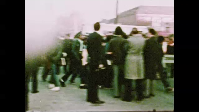 1970s: UNITED STATES: people dangle from burning building. Building on fire. Do Not Cross tape. Press gather at incident