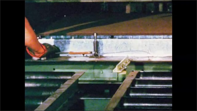 1960s: UNITED STATES: fibre board attached to frame. Men place fibre board in press. Barbs on plate.
