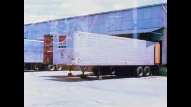 1960s: UNITED STATES: men load pre fabricated building into truck. Truck in factory. Truck arrives at home. Man opens truck door