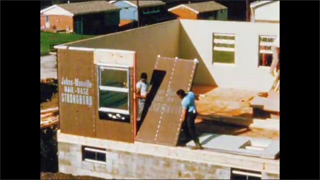 1960s: UNITED STATES: labourers install panel in building. Pre fabricated building
