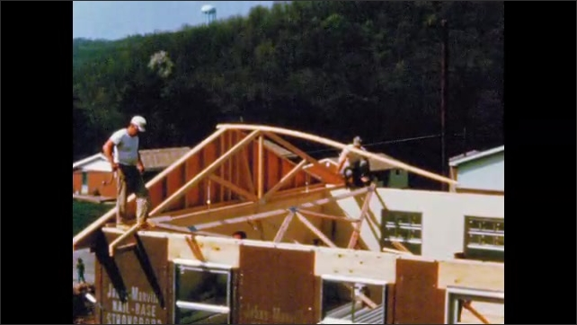 1960s: UNITED STATES: crew install truss on new building. Pre fabricated building on site