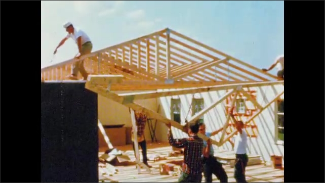 1960s: UNITED STATES: Hands position truss into notch. Man hits truss with hammer. Workers lift cross into place. Men build roof on house