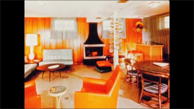 1960s: Living room in orange, sofas and a small table, fire place, bar and dining table. Living room with dining table, desk, armchair, sofa, small table and a large window.
