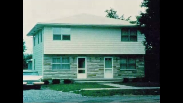 1960s: Two story duplex home with garage and front lawn. Car parked on driveway next to duplex home.