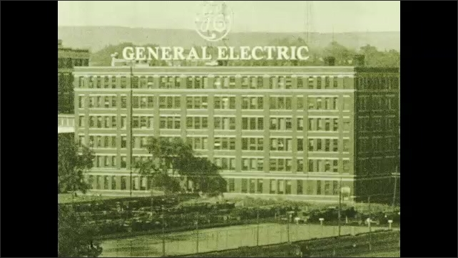 1930s: Train yard next to brick buildings including the General Electric building. Interior of the GE plant, with large turbines and mechanics.