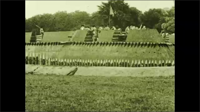 """1930s: Fort Stanwix in Rome, New York. Reenactors perform on the fort, including shooting a cannon. Intertitle """"Here, the American flag , with its stars and stripes , was first raised""""."""