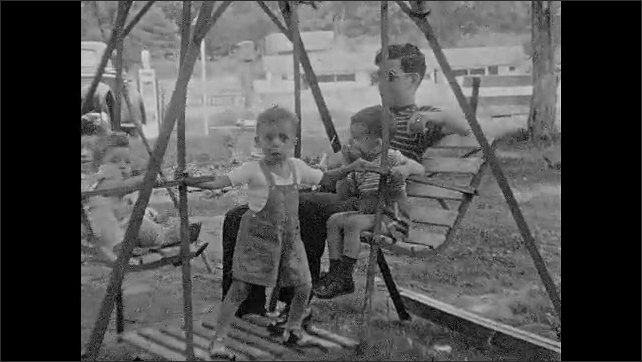 1930s: UNITED STATES: man films with camera. Man sits with children on swing seat. Man stands by wood pile.
