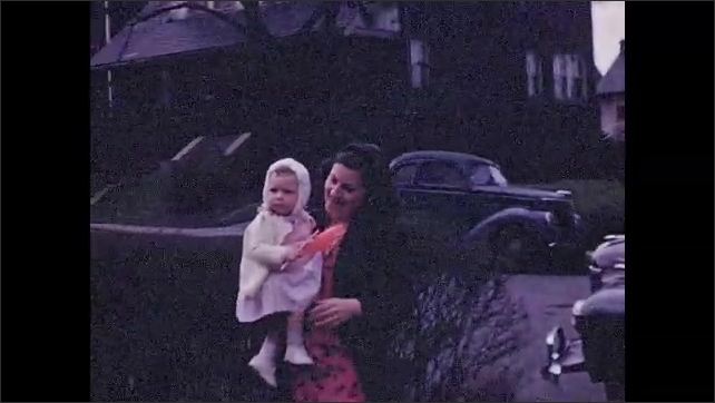 1940s: UNITED STATES: child with paper windmill. Lady carries baby. Toddler with red hair