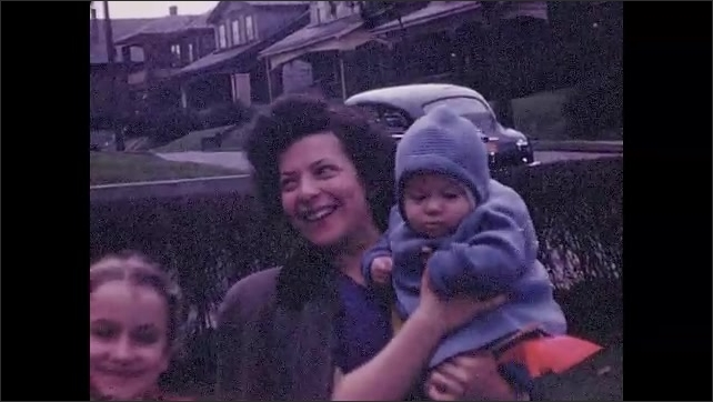 1940s: UNITED STATES: woman holds baby. Man smiles at camera. Boy with curly blonde hair.