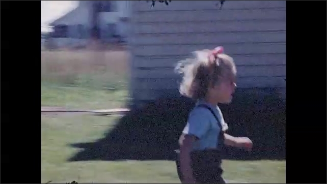 1940s: UNITED STATES: toddlers play in garden. Boy looks at camera. Baby runs to girl in deckchair. Children on stools in garden
