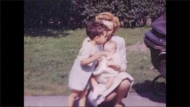 1940s: UNITED STATES: boy kisses baby in garden. Lady holds baby by pram. Boy holds glass of milk. Boy drinks milk. Boy kisses sister