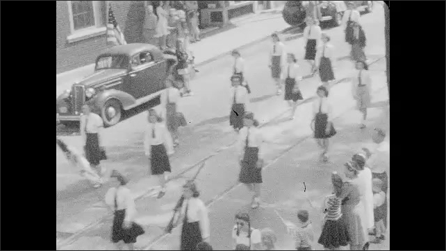 1930s: UNITED STATES: uniformed women in parade. Nurses march in parade. Car follows ladies in street.