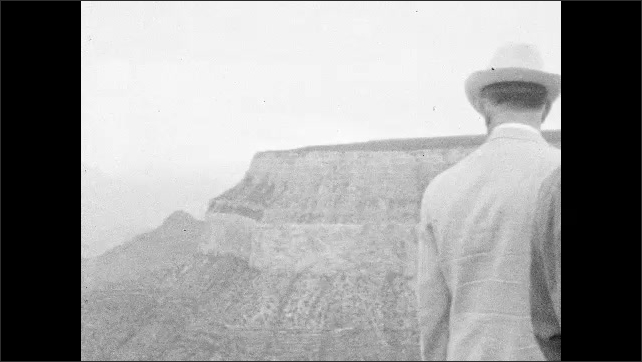 1930s: Men in suits and hats look over canyon. Desert mesas and hills.