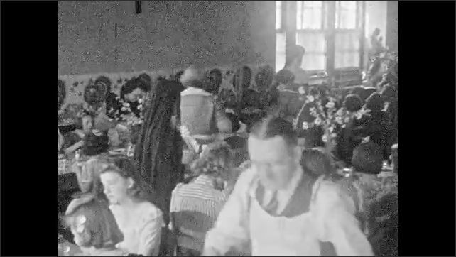 1930s: Girls sit at table eating dinner. Waiters and nun bring food to the table.