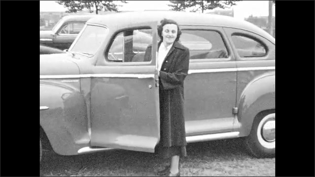 1930s: Men in suits laugh and lean against parked car. Woman stands next to open door of car. Fence, wooden buildings and outhouse.