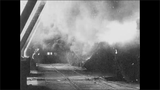 1930s: Men work in steel mill.  Machines.  Sparks fly.