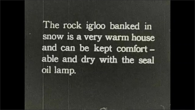 1930s: Title card. Igloo made of rock in hillside. Title card. Group of people enter rock igloo covered in snow.