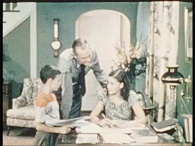 1950s: The father walks and puts his hand on the son????s head. The daughter talks to her brother, the father observes the documents on the desk. The father talks to son and tousles his hair.