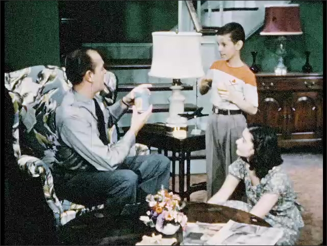 1950s: Cans pass through canning machine. Son holds glass with juice and gives a can to his father who sits in an armchair. Father talks to daughter who sits on the floor and points to can.