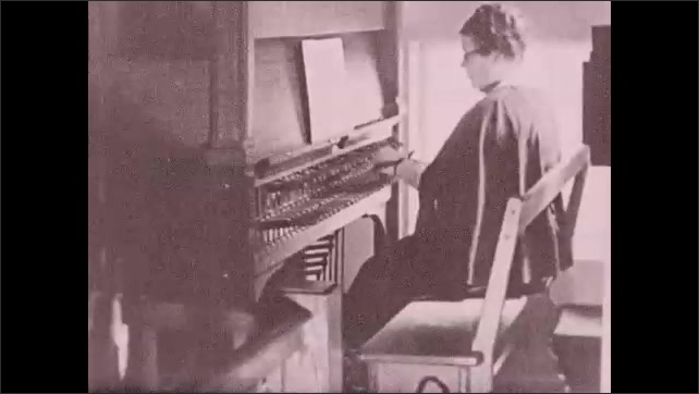 1930s: UNITED STATES: close up of hands on carillon keys. Lady plays carillon chimes. Bell strikes.